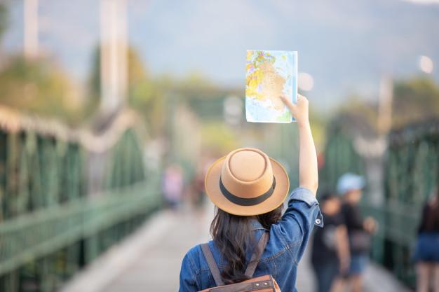 mujeres-turistas-mano-tienen-feliz-mapa-viaje_1150-7411